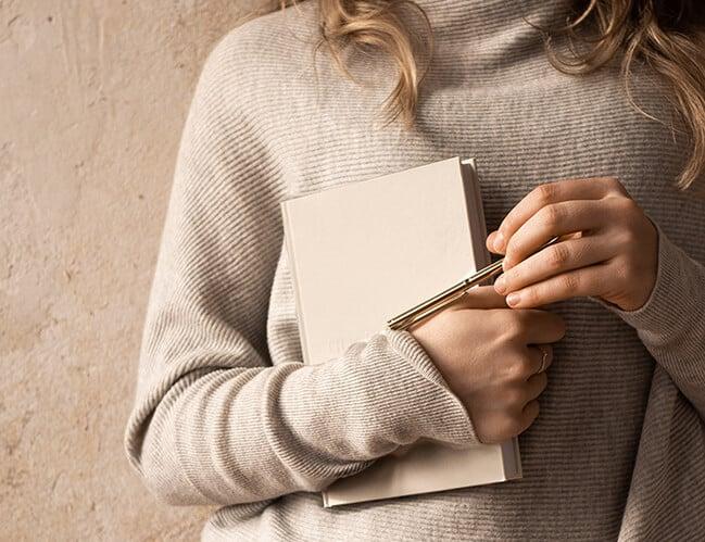 woman in beige jumper holding a book